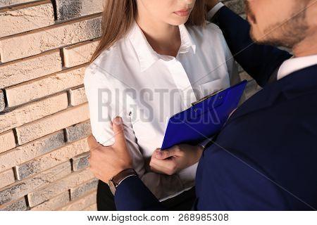 Boss Molesting His Female Secretary Near Brick Wall, Closeup. Sexual Harassment At Work