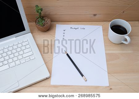 Paper Check List For Budget, Laptop, Coffee On Wooden Table. Budget Check List For Financial Plannin