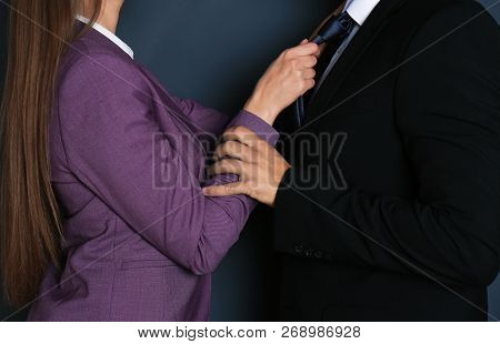 Woman Molesting Her Male Colleague On Dark Background, Closeup. Sexual Harassment At Work