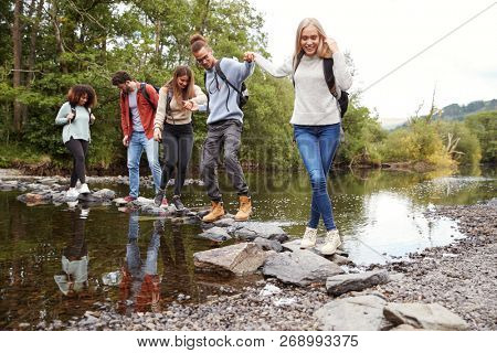 Multi ethnic group of five young adult friends hold hands walking on rocks to cross a stream during a hike