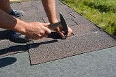 Roofer installing Asphalt Shingles  on house construction roof corner with hammer and nails. Roofing construction with Asphalt Shingles. poster