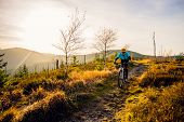 Cycling woman riding on bike in autumn mountains forest landscape. Woman cycling MTB flow trail track. Outdoor sport activity. poster