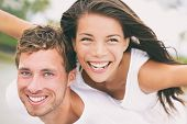 Happy couple having fun piggybacking laughing on summer honeymoon holidays vacation on beach. Beautiful interracial multi-ethnic dating people on wedding, Caucasian man and Asian woman. poster