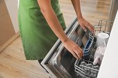 Woman opening dishwasher in kitchen, closeup. Cleaning chores poster