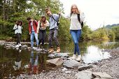 Multi ethnic group of five young adult friends hold hands walking on rocks to cross a stream during a hike poster