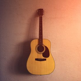 Old Acoustic Guitar On A Sandy Texture. Sunlight.