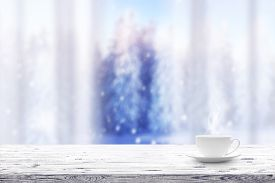 Cup With Hot Drink On Wooden Table And Window Over Winter Snow Covered Forest Background