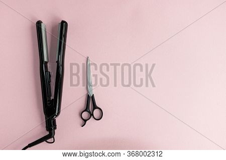 Hair Straightener With Scissors On A Pink Background Close-up.  Hair Care Tools.