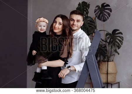 Portrait Of Beautiful Young Parents And Their Cute Little Daughter Hugs, Looking At Camera And Smili