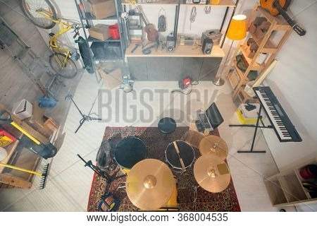 Drumset on the carpet, pianoboard, guitar and other musical instruments, laptop, worktools, wooden shelves and other stuff in garage