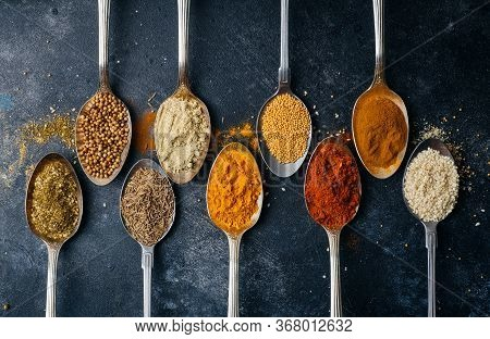 Spices In Spoons Background. Varieties Of Spices (turmeric, Pepper, Chili, Coriander, Cinnamon) And