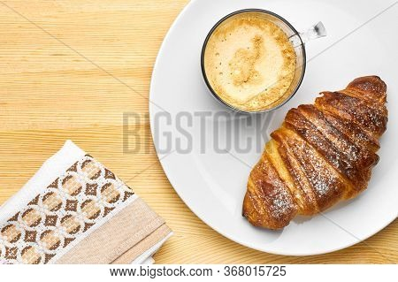 Top View On A Breakfast Consisting Of A Cup Of Coffee, A Croissant On A Wooden Table With Copy Space