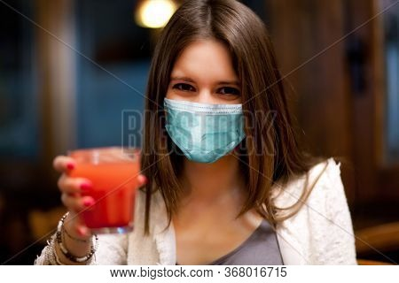 Beautiful woman having a drink at the pub wearing a mask, coronavirus concept