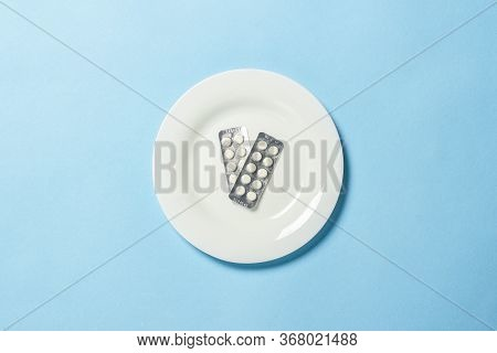 Two Plates With Pills On A White Plate On A Blue Background. Insomnia, A Choice Of Drugs, Vitamins,