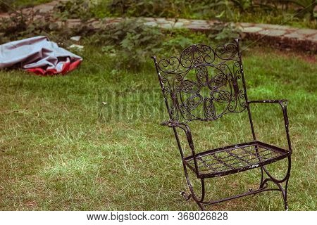 Hand Crafted Wrought Iron Bench In A Lush Green Park