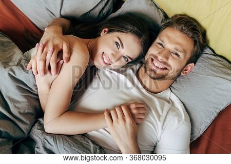 Top View Of Happy Couple Hugging In Bed And Looking At Camera