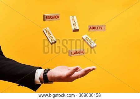 Learning Skills Concept. A Man Throws Up Wooden Blocks With The Inscriptions Skill, Knowledge, Abili