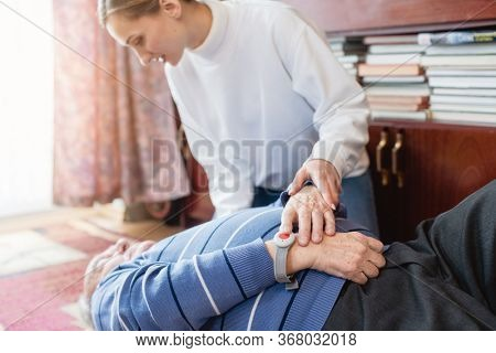 Nurse in assisting living program finding senior man lying on the floor