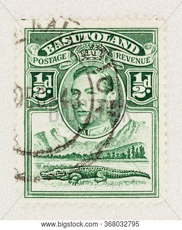 Seattle Washington - May 23, 2020:  Green 1938 Basutoland Stamp Featuring Nile Crocodile By River An