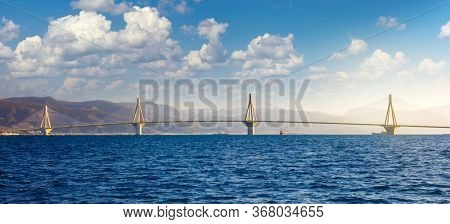 Panoramic view of Modern Bridge with white clouds.  Rion-Antirion Bridge, Greece, Europe. The Rion-Antirion Bridge in Greece one of the longest of the fully suspended type bridge