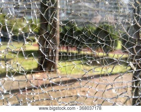 A View Into Garden Through A Broken Glass Window