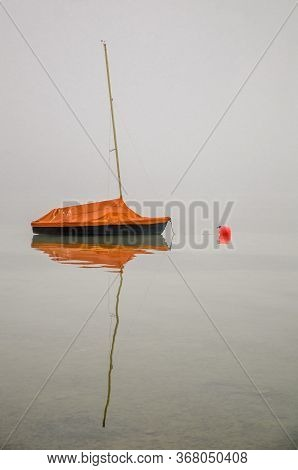 Moored Sailboat In The Fog Reflecting On A Calm Water Surface At Lake Constance, Germany