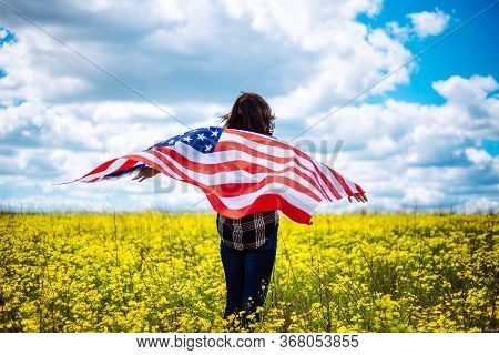 Patriotic Young Woman Flies An American Flag On A Beautiful Field With Yellow Flowers. Usa Independe