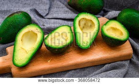 Halves Fresh Avocado, Ripe Avocado And Cut Avocado With Bone. Ripe Autumn Pears In A Wooden Crate