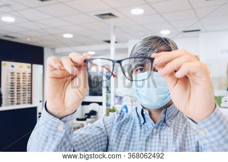 Middle-aged Man Wearing Sanitary Mask Holding Elegant Glasses In His Hands At An Optician's. Selecti