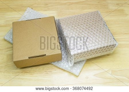 Bubbles Covering The Box By Bubble Wrap For Protection Product Cracked On Wood Table