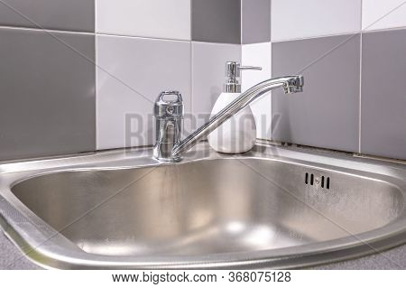 Soap And Shampoo Dispensers Near Ceramic Water Tap Sink With Faucet In Expensive Kitchen