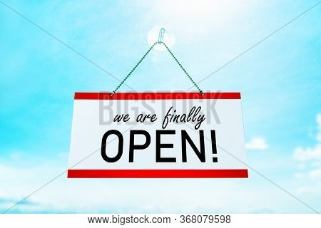 COVID-19 WE'RE FINALLY OPEN ! sign hanging on window store end of confinement stores reopening . Retail businesses opening again for non essential services. Sunny summer background.
