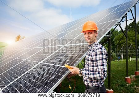 Male Engineer With A Sensor In His Hands, Looking To The Camera Near The Solar Panels Which Reflect