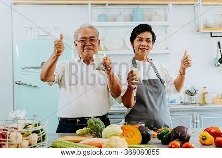 Happy Asian Senior Couple Drinking Milk At Home. 70s Elderly Married Man And Woman Giving A Thumbs U