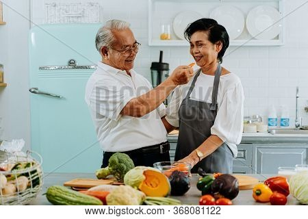 Senior Asian Couple Grandparents Cooking Together While Woman Is Feeding Food To Man At The Kitchen.