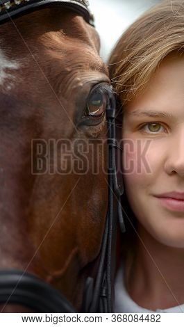 Girl's And Horse's Eyes. Portrait Of A Pretty Young Girl With A Browne Horse Close-up Fragment.
