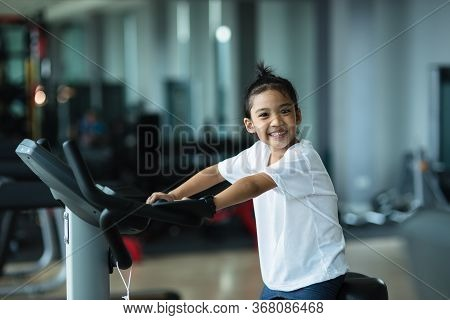 A Little Girl Using Exercise Bike At The Gym. Fitness Female Using Air Bike At Gym.