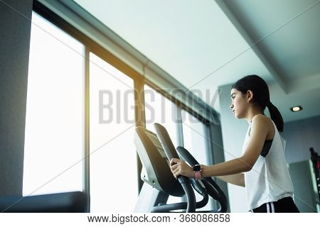 Asian Girl Exercise Elliptical Cardio Running Workout At Fitness Gym Taking Weight Loss With Machine