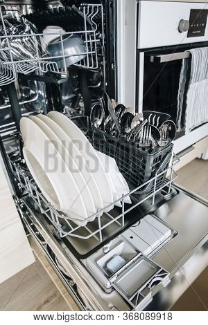 Colorful Dishwasher Detergent Tablet For Dishwashing Machine. Open Dishwasher With Clean Glasses And