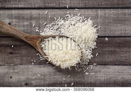 Closeup Uncooked Dry Thai Jasmine Rice Are Overflow In Wooden Ladle On Wooden Floor, Flat Lay And To
