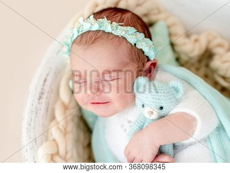 Charming smile of sleeping newborn hugging toy