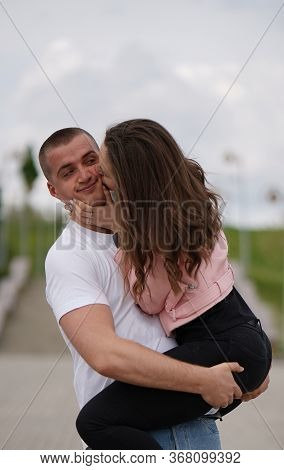 Kissing Couple In Park, Strong Man Holding Girl On Arms, Woman Kissing Him . Kiss, Love And Relation
