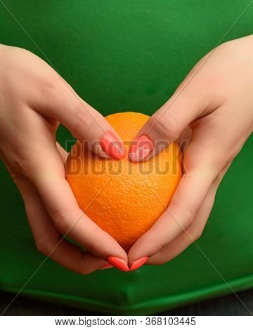 A Girl With A Beautiful Orange Manicure Is Holding A Ripe Orange In Her Hands. Close-up Photo.