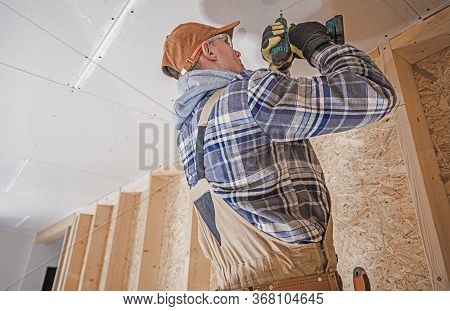 Caucasian Construction Contractor With Electric Drill Driver Attaching Drywall Elements To The House