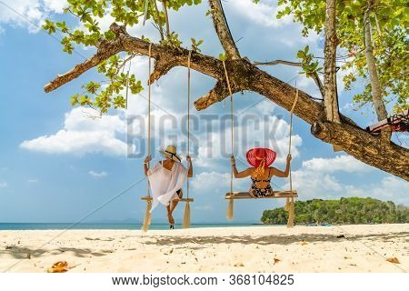 Two beautiful Women on a swing at the beach in Thailand