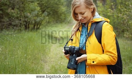 Portrait Of Delighted Woman Standing In Green Leafy Forest Reviewing Recent Images On Her Dslr Camer