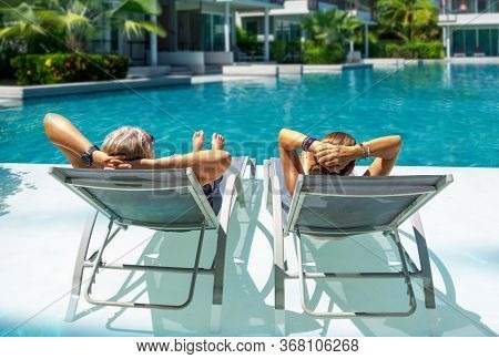 Couple in luxury five stars  spa resort by the swimming pool.