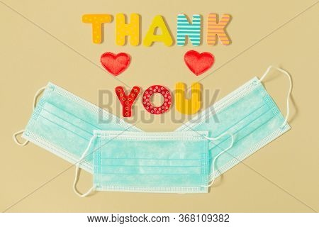 Appreciation To Medical Staff. Words Thank You Of Wood Letters, Heart Symbols And Medical Masks In S