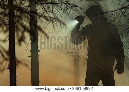 Rescue Search. Men Wearing Camouflage Clothing With Powerful Flashlight Between Trees And Fire Smoke