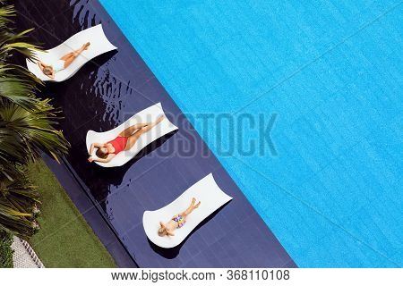 Young Mother, Kids Relax On Sun Beds At Swimming Pool In Luxury Spa Resort Or Villa. Top View. Touri